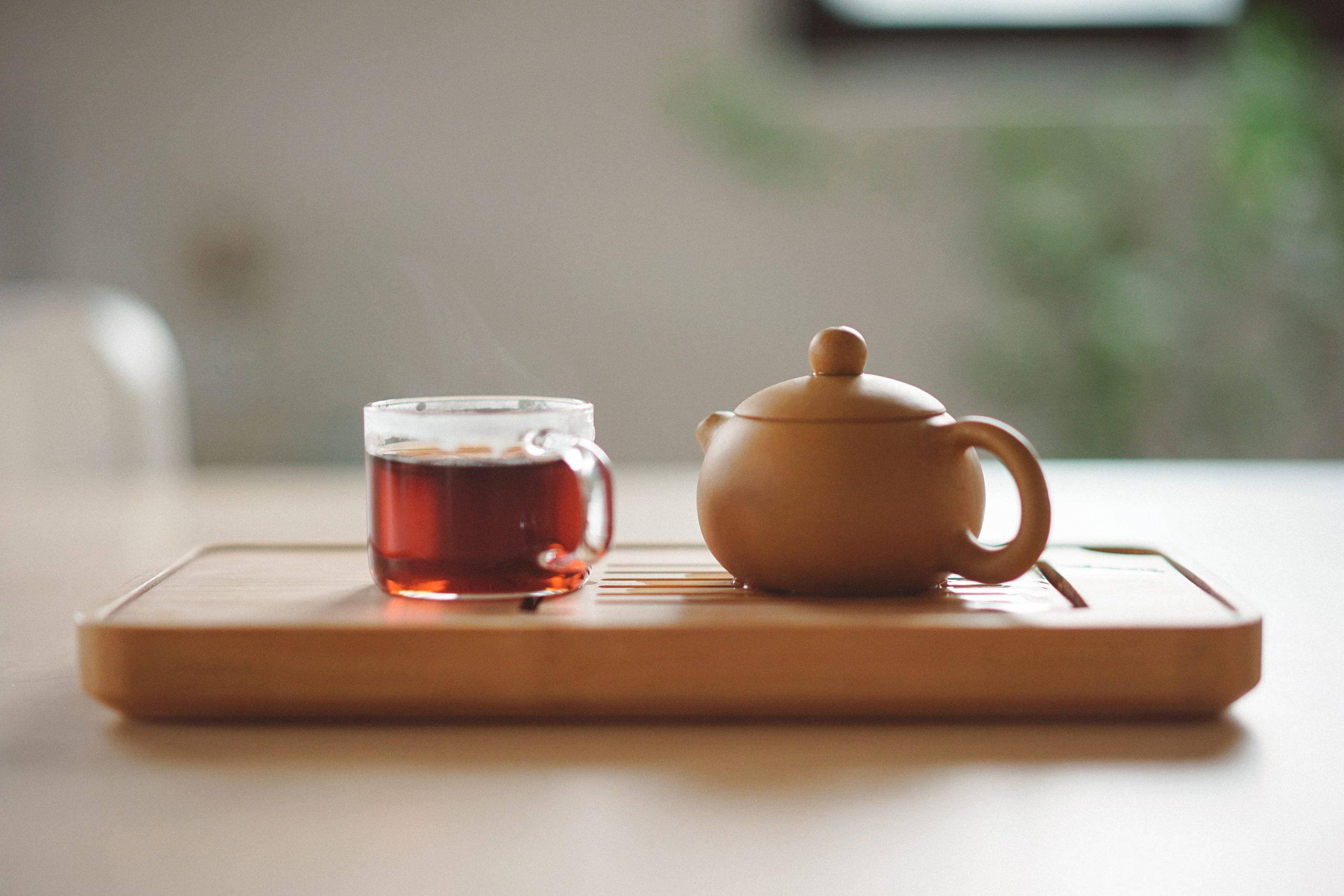En te kopp och tekanna står på ett bord med suddig bakgrund